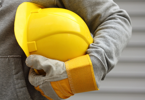 Operaio con casco giallo sotto al braccio