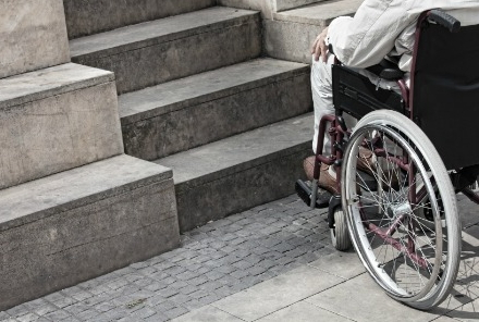 Disabile su sedia a rotelle di fronte a rampa di scale