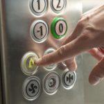 Più sicurezza coi sistemi di teleassistenza e telesoccorso negli impianti elevatori Dito che preme pulsante di emergenza di ascensore